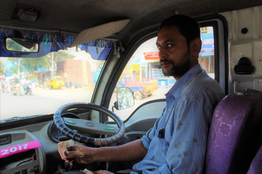 Taxi-bus driver looks suspiciously at camera. He later smiles.